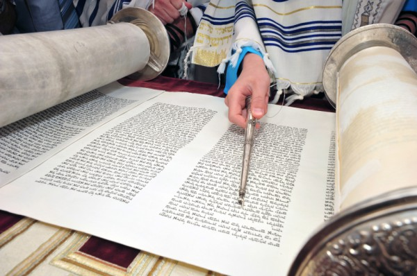 Reading the Torah scroll with a pointer called a yad (literally, hand).