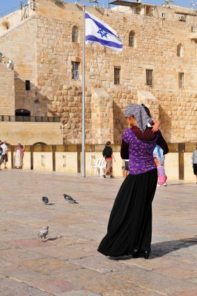 An Orthodox Jewish woman carries her child across the Promenade in front of the Kotel