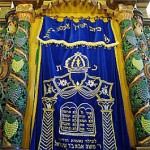 The Parokhet (embroidered curtain) can be either inside or outside the Aron Kodesh (Holy Ark).