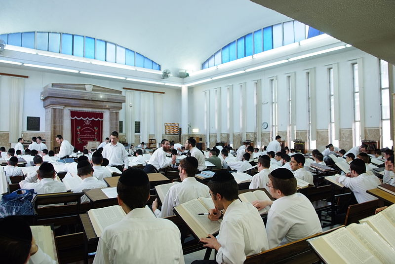 Jewish young men studying at a yeshiva, an Orthodox Jewish institution of learning.