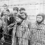 Child survivors of Auschwitz stand behind barbed wire fence wearing adult-sized prisoner jackets.