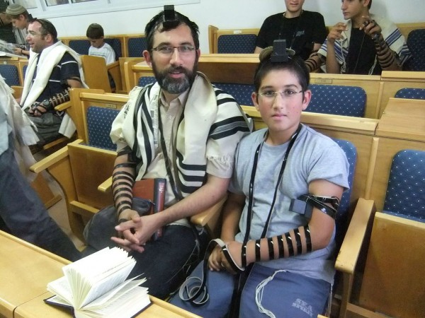 A father and son wear tefillin, which symbolize devotion to God and the Torah, during morning prayers.