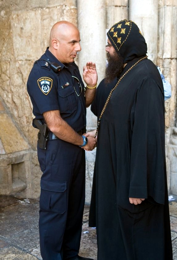 Coptic-priest-speaks-with-an-Israeli-police-officer-at-the-Church-of-the-Holy-Sepulcher-in-Jerusalem