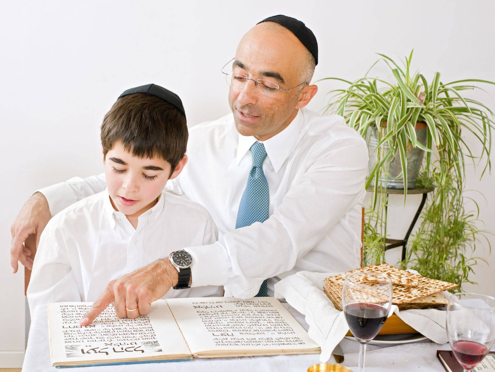 A Jewish father reads a Hebrew Haggadah with his son during the Passover Seder.