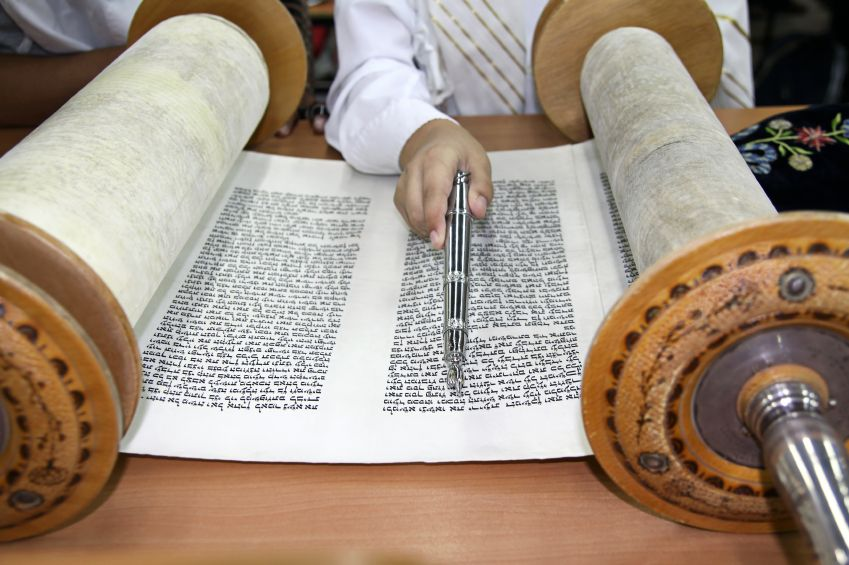 Reading from the opened Sefer Torah (Torah scroll) using a yad (Torah pointer) to follow along in order to protect the precious parchment and handwritten text. The yad also allows others to see the text and ensure that the Torah is read without mistakes.