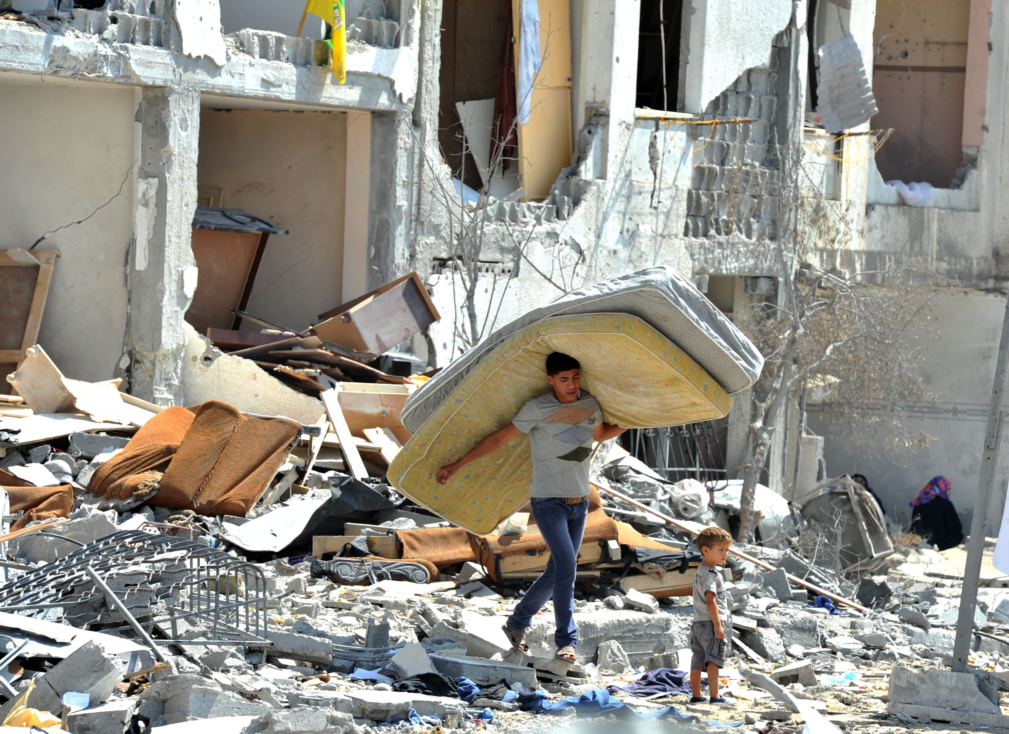 A Palestinian searches through rubble of his destroyed home in Towers Al-andaa in the northern Gaza Strip.