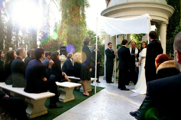 A Jewish bride and groom exchange vows under the chuppah.