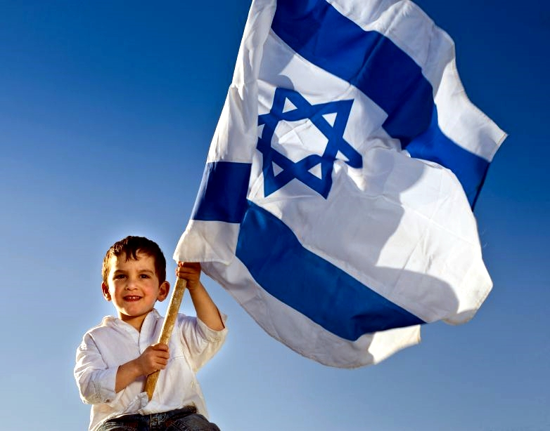A Jewish lad holds the flag of the State of Israel.