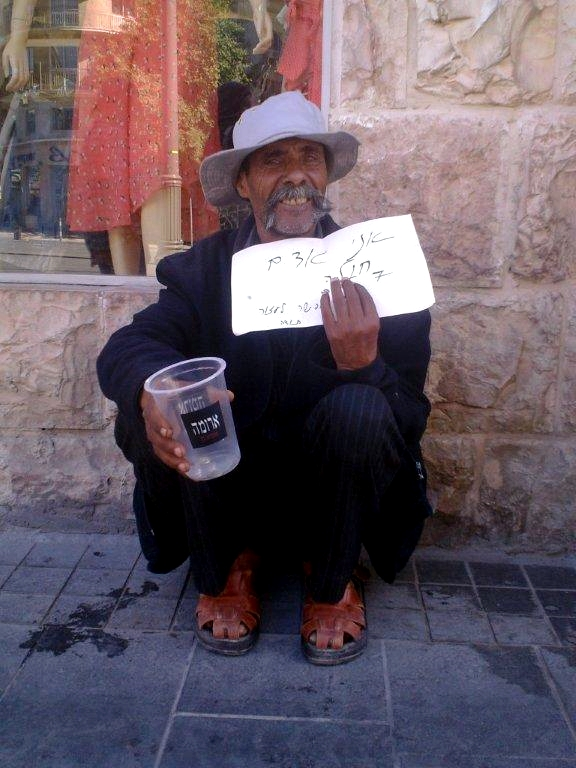 A homeless man begs on the street in Israel.