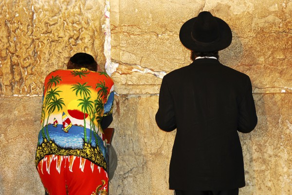 An Orthodox Jewish man and a tourist stand side by side at the Western (Wailing) Wall praying fervently.