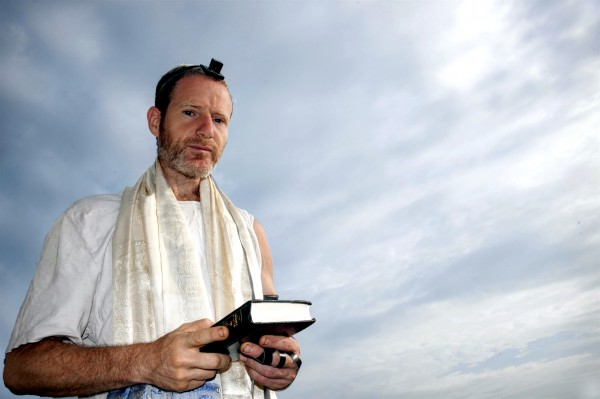 A Jewish man prepares to recite morning prayer.