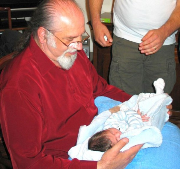 An Israeli grandfather holds his grandchild after the Brit Milah.