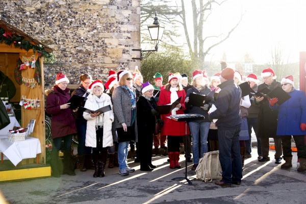 Members of the Winchester Musicals and Opera Society sing carols at Winchester Cathedral in England.