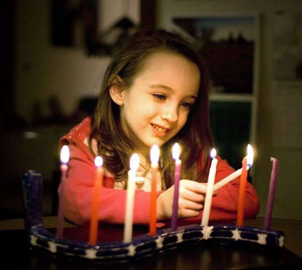 A young Jewish girl admires the light of the fully lit Chanukah menorah.