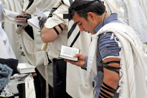 Jewish men wearing tallitot (prayer shawls) pray with tefillin (phylacteries) and siddurim (Jewish prayer books).