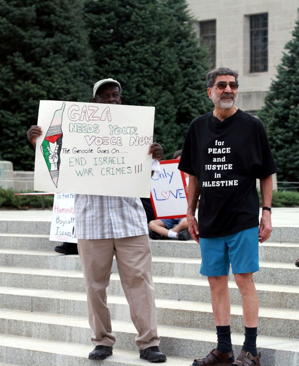 An anti-Israel protester holds a sign falsely accusing Israel of genocide and war crimes. The map on the sign reveals the ambition to wipe out Israel and for a Palestinian state to replace it. The sign behind him on the left tells passersby to boycott Israel.