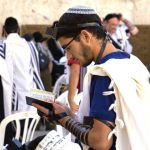 A Jewish man wearing a kippah, tefillin (phylacteries), and a tallit (prayer shawl) prays at the Western (Wailing) Wall using a siddur (prayer book).