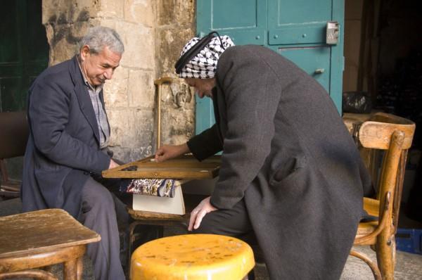 Two Arab men enjoy a game of Backgammon at a Jerusalem cafe.