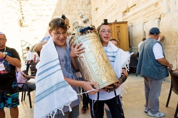 Two 13-year-old Jewish boys share the weight of carrying a Torah scroll encased by a silver Torah tik.