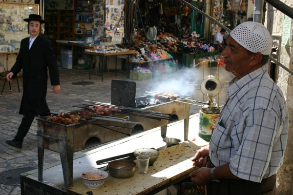 A Hassidic teenager glances toward an Arab grilled-meat stand in Jerusalem.