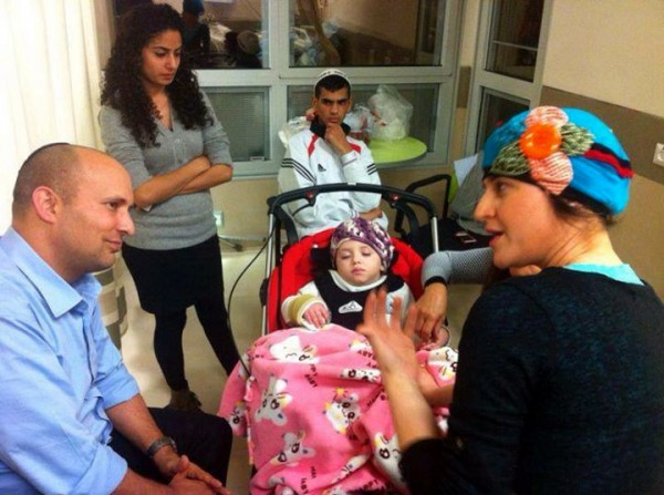 Naftali Bennet speaks with Adva Biton. while young Adele rests in a stroller.