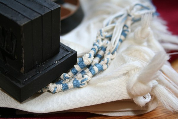 The black box of tefillin (which contains Scripture) and the tzitzit with the tekhelet (blue thread) of the tallit.