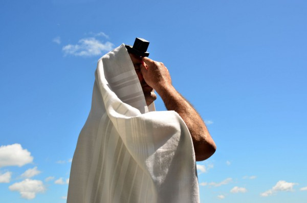 A Jewish man prays wearing a tallit (prayer shawl) and tefillin (phylacteries).