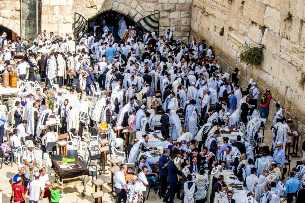 Men gather to worship God at the Western (Wailing) Wall. On close inspection, at least 20 Torah scrolls are either being carried or are placed on tables in the above photo.