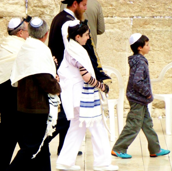 A 13-year-old Jewish boy carries the Torah scroll publicly for the first time at the Western (Wailing) Wall in Jerusalem.
