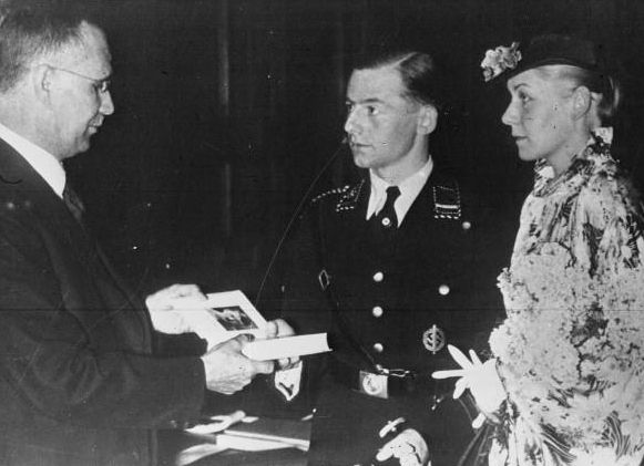 Chancellor Hitler gives a copy of his book Mein Kampf to a newlywed couple during a wedding ceremony in Germany in 1936. Every couple was to receive a copy of it on their wedding day.