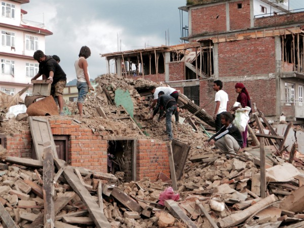 People rummage through the ruins of their home following the earthquake in Nepal.  (Photo by SIM Central and Southeast Asia)
