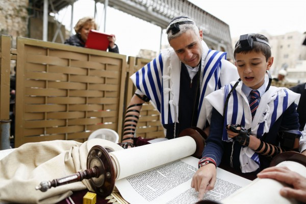 A 13-year-old Jewish boy wearing tefillin (phylacteries) and a tallit (prayer shawl) reads from the Torah at the Western (Wailing) Wall. (Israel Ministry of Tourism photo by Yonatan Sindel, Flash 90)