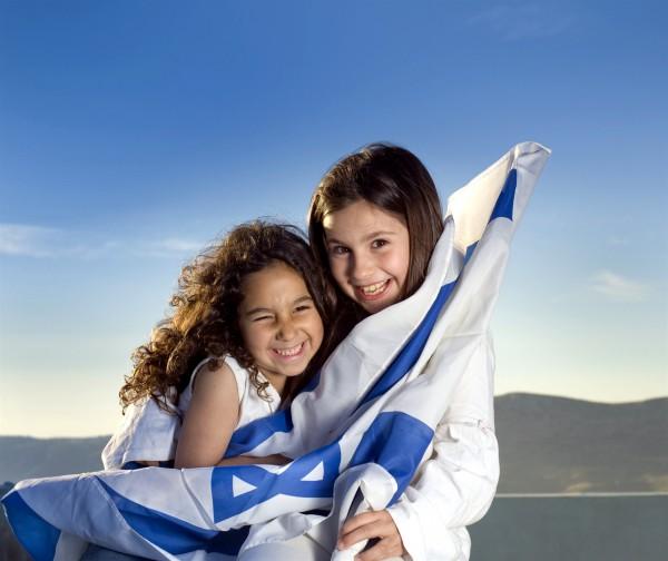 Two Israeli girls hold the Israeli flag.