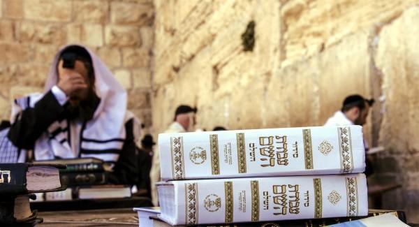 Jewish men pray Shacharit (morning prayers) at Jerusalem's Western (Wailing) Wall. In the foreground are siddurs (Jewish prayer books).