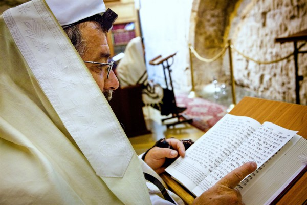 A Jewish man wears a tallit (prayer shawl) and tefillin (phylacteries) as he prays using a siddur (Jewish prayer book) at the Western (Wailing) Wall in Jerusalem.