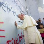 Pope Frances prays at the separation barrier
