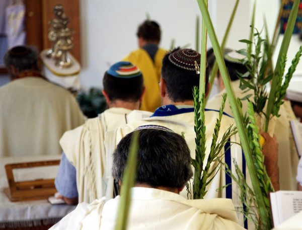 Jewish men pray in a synagogue on Sukkot. They are holding Sukkot's Arba'ah Minim (Four Kinds of plant), which are mentioned in Leviticus 23:40.