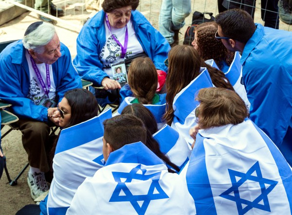 Teens wrapped in Israeli flags at the Auschwitz extermination camp listen to the testimony of Holocaust survivors.