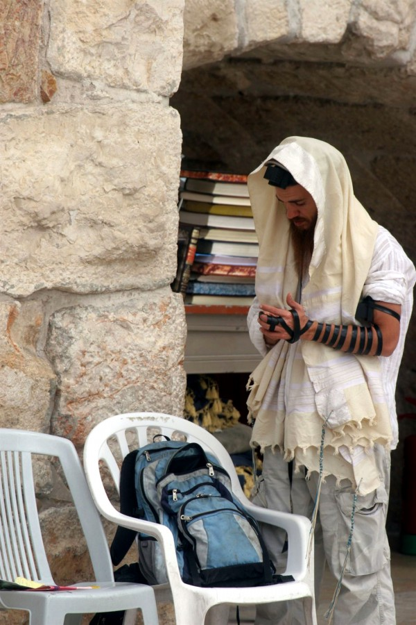 A Jewish man wearing a tallit (prayer shawl) and tefillin (phylacteries) prays at the Western Wall in Jerusalem.