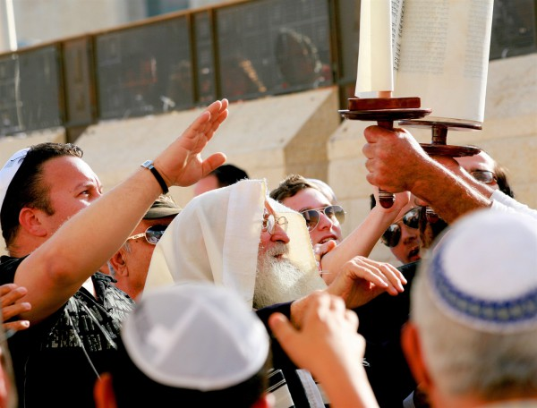 Jewish men pay respect to the Torah scroll at the Western (Wailing) Wall.