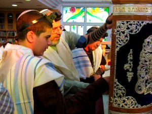 A Jewish 13-year-old male reads from a Torah scroll protected by an elaborately decorated Torah tik.