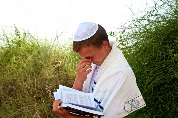 A Jewish teen wearing a tallit (prayer shawl) and a kippah (head covering) prays using a siddur (prayer book).
