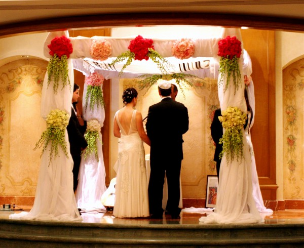 A Jewish bride and groom say their vows underneath the chuppah. (Photo by Greg Hirson)