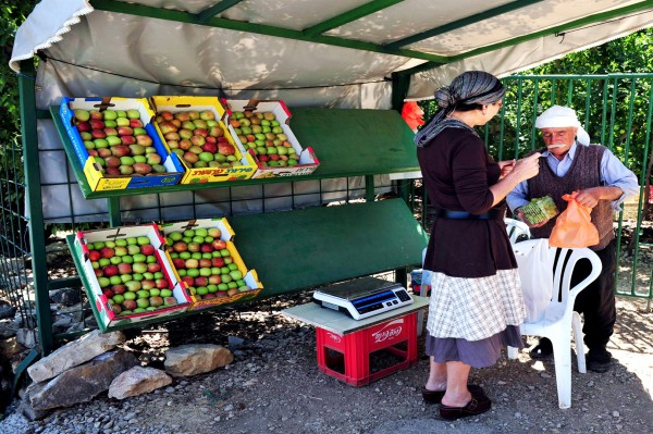 A Jewish woman buys fruit from a Druze Muslim in the Golan Heights.