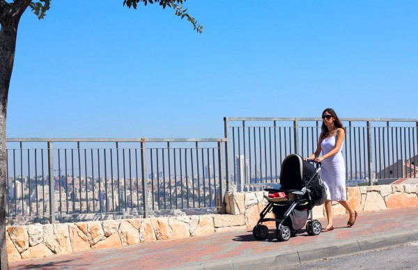 A mother pushes her infant in a stroller on a street in Jerusalem.
