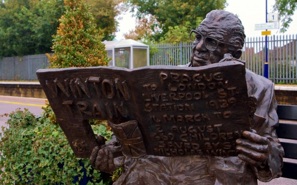 This sculpture on platform three of the Maidenhead train station by  Lydia Karpinska depicts Sir Nicholas relaxing on a park bench,  reading a book that contains images of the children he saved and  the trains used to evacuate them. (Photo by Porsupah Ree)