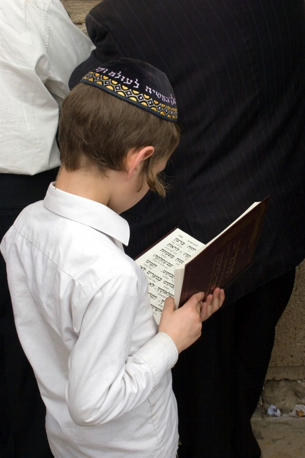 A Jewish boy reads the Jewish prayer book at the Western (Wailing) Wall.