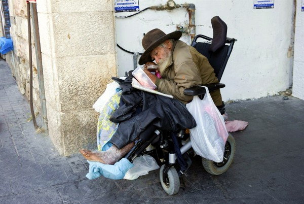 A homeless man in a wheelchair on a Jerusalem street.