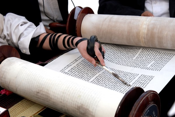 A Jewish youth wearing tefillin (phylacteries) reads from the Torah scroll, keeping his place with a yad (Torah pointer).