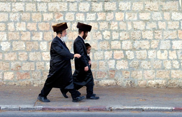 Two Jewish men and a boy walk together in Israel.
